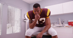 学院等在医生的办公室的足球运动员坏消息 免版税图库摄影