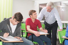 学院老师帮助他的学生 免版税图库摄影