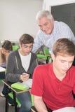 学院老师帮助他的学生 免版税库存照片