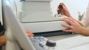 医学高技术-验光师设备在使用中-普通眼睛扫描器机器 免版税库存照片