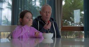 学龄前与她的祖父的女孩品尝新鲜的草莓 影视素材