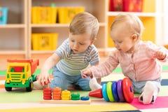 学龄前使用在与教育玩具的地板上的男孩和女孩 孩子在家或托儿 免版税图库摄影