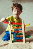 学龄前儿童婴孩学会计数 使用与算盘玩具的逗人喜爱的孩子 获得的小男孩乐趣户内在家 免版税库存照片