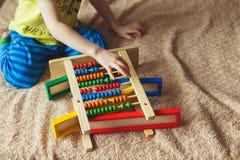 学龄前儿童婴孩学会计数 使用与算盘玩具的逗人喜爱的孩子 获得的小男孩乐趣户内在家 图库摄影