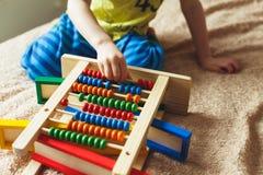 学龄前儿童婴孩学会计数 使用与算盘玩具的逗人喜爱的孩子 获得的小男孩乐趣户内在家 库存照片