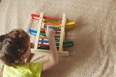 学龄前儿童婴孩学会计数 使用与算盘玩具的逗人喜爱的孩子 有的小男孩乐趣户内在家,幼儿园或者天c 库存照片