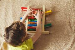 学龄前儿童婴孩学会计数 使用与算盘玩具的逗人喜爱的孩子 有的小男孩乐趣户内在家,幼儿园或者天c 免版税库存图片