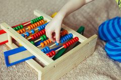 学龄前儿童婴孩学会计数 使用与算盘玩具的逗人喜爱的孩子 有的小男孩乐趣户内在家,幼儿园或者天c 免版税库存照片