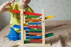 学龄前儿童婴孩学会计数 使用与算盘玩具的逗人喜爱的孩子 有的小男孩乐趣户内在家,幼儿园或者天c 库存图片