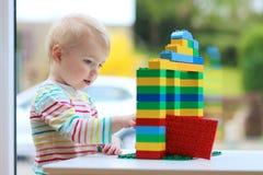 学龄前儿童从塑料砖的女孩大厦 免版税库存照片