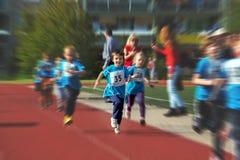 年轻学龄前孩子,跑在马拉松competi的轨道 库存图片