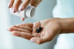 医学 女性手倾吐的药片特写镜头到棕榈里 免版税库存图片