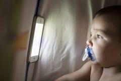 婴孩与手机的观看的催眠曲动画片在小儿床 图库摄影