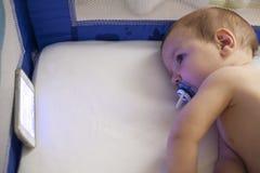 婴孩与手机的观看的催眠曲动画片在小儿床 免版税库存图片