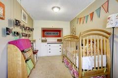 婴孩与木小儿床的室内部 库存图片