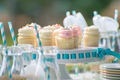 婴孩与瓶的生日装饰牛奶和杯形蛋糕 免版税库存图片