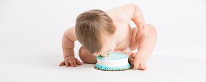 婴孩倾斜的面孔到蛋糕里 免版税图库摄影