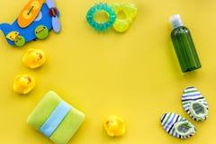 婴孩关心辅助部件、玩具和衣物在黄色背景顶视图嘲笑 免版税库存图片