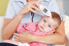 婴孩和一个数字体温计 免版税图库摄影