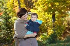 婴孩和她的母亲在秋天期间 库存图片