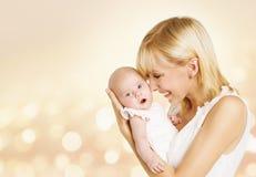 婴孩和母亲,与妈妈的新出生的孩子,抱孩子的愉快的妇女 免版税库存照片