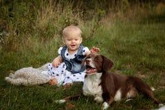 婴孩和狗在湖 图库摄影