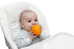 婴孩咬住的桔子 免版税库存照片