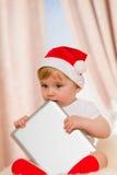 婴孩圣诞老人拿着一种片剂 免版税库存照片