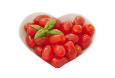 婴孩在一个心形的碗的李子tomates 免版税图库摄影