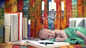 婴孩在与书和烛台的一个集合睡觉 股票视频