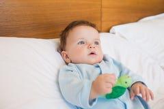 婴孩在床上的拿着玩具 免版税库存照片