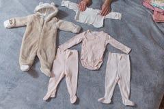 婴孩在床计划的` s衣裳,自然光上 免版税库存图片