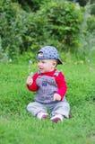 婴孩在手中坐草在有花的公园 免版税库存图片