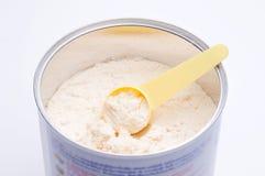 婴孩在打开与匙子的罐头的奶粉 免版税库存图片