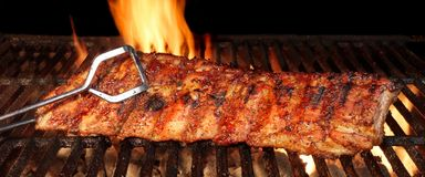 婴孩在热的火焰状格栅的后面或猪肉排骨 免版税库存图片