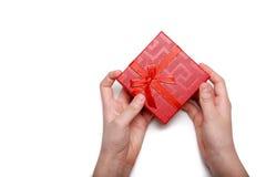 婴孩在白色背景递拿着一个红色礼物盒被隔绝 顶视图 免版税库存图片