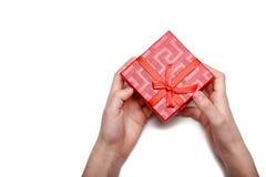 婴孩在白色背景递拿着一个红色礼物盒被隔绝 顶视图 免版税库存照片