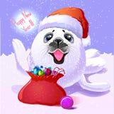 婴孩在盖帽圣诞老人的海狗和与愉快的礼物的一个袋子 库存照片