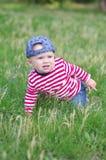婴孩在草爬行在夏天 库存图片
