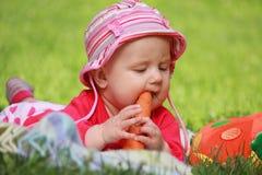 婴孩在他的手上的拿着一棵红萝卜 库存图片