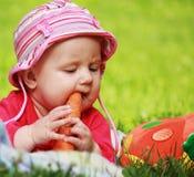 婴孩在他的手上的拿着一棵红萝卜 库存照片