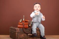 婴孩坐手提箱在老电话附近 库存图片