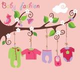 婴孩垂悬在树的出生的衣裳。 免版税图库摄影