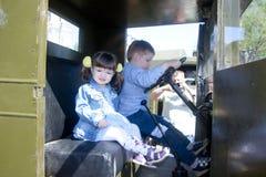 孩子、小女孩和男孩在一辆老军用卡车的驾驶舱内 库存图片