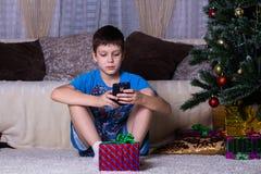 孩子、技术、互联网通信和人概念-有智能手机正文消息或在家使用比赛的男孩,新 免版税图库摄影