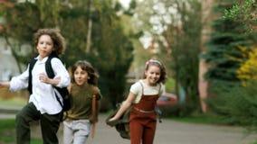孩子、男孩和女孩从学校跑,挥动挑运 乐趣假日 回到学校 儿童天 股票视频