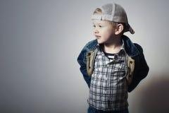 孩子。牛仔裤的滑稽的小男孩。卡车司机盖帽。喜悦。时兴的孩子。格子花呢上衣。牛仔布穿戴 库存图片