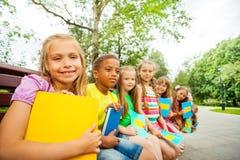 孩子一起坐与书的棕色长凳 免版税图库摄影