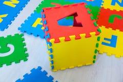 孩子七巧板的五颜六色的教育地毯,是时兴的收集在有英语字母表的箱子,教 免版税库存图片