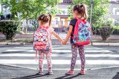 孩子上学,有学校背包的愉快的学生和结合手 图库摄影
